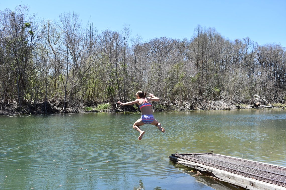 Girl jumping into the Guadalupe River in Ingram Texas