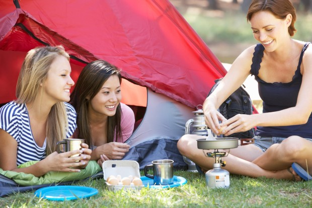 Three Young Women Cooking On Camping Stove Outside Tent